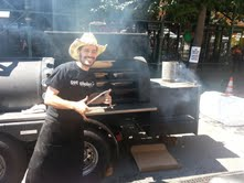 Ari WHite in front of his portable truck where he smokes his meat for days at a time.